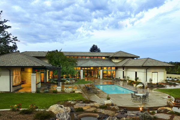 rear elevation of a custom home with a pool