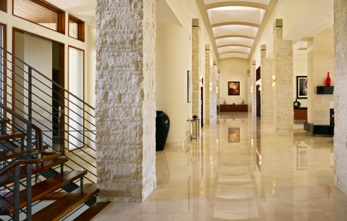 long marble finished hall way with native stone columns that flank it leading to a clerestory