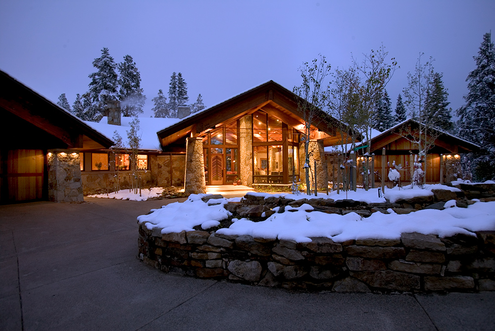 front view of a custom home in a mountain setting, well lite entry, snow in front.