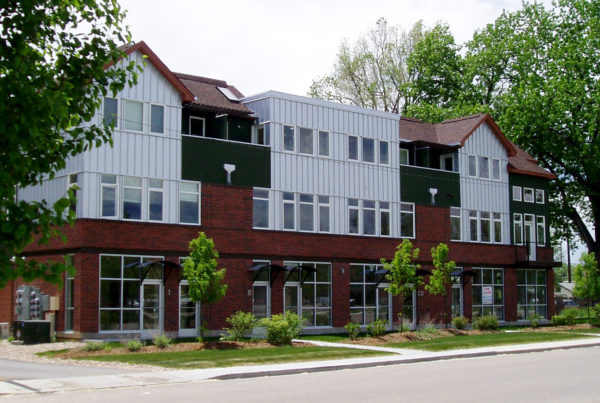 contemporary multi-use building with vertical aluminum siding and a red brick exterior on the first floor of the three levels